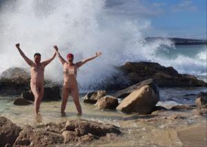 Chono und Tandana nackt in der Brandung zwischen Lavafelsen und einer Riesen-Welle